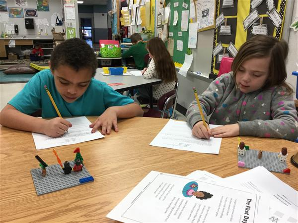 Students work with Legos to build scenes and write about them.