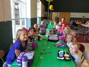 Character Trait of the Month Students eat lunch in the cafeteria at a decorated table.